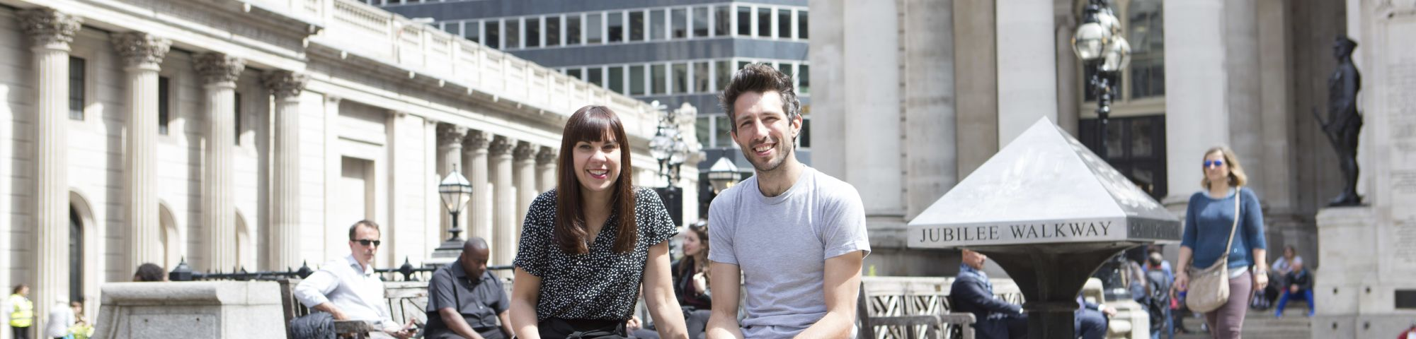 2 people sat on a multicoloured bench in London