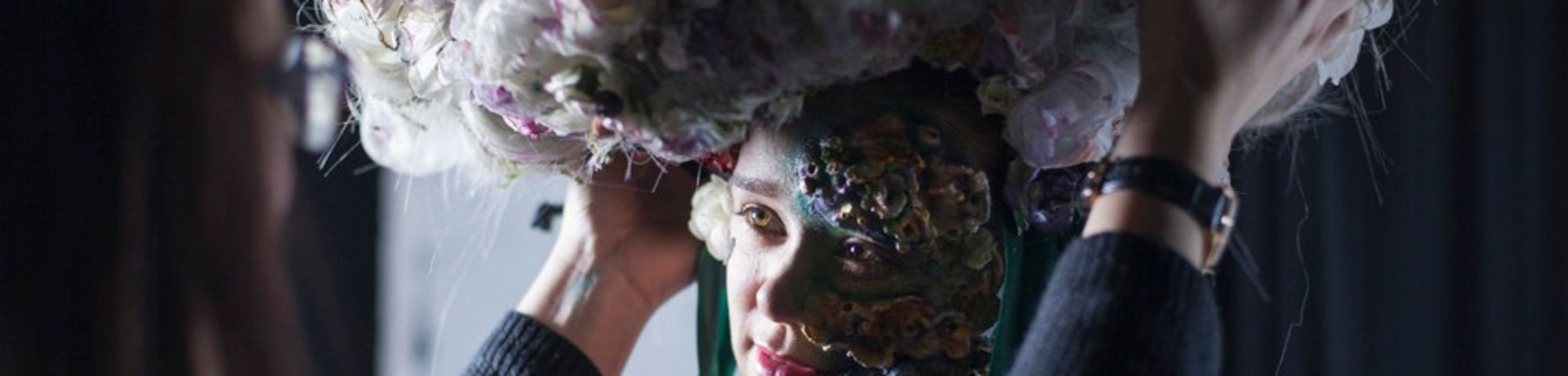 A model having a large floral headpiece adjusted on her head