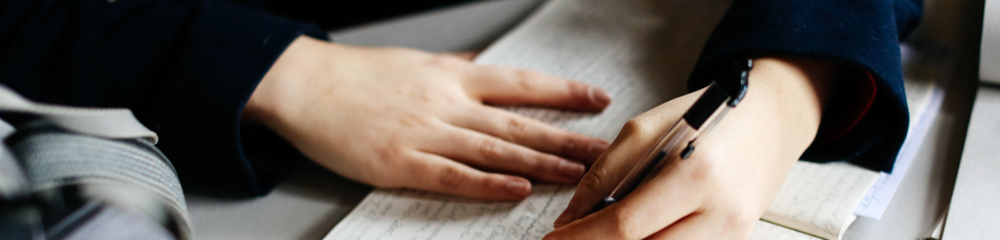 Hands writing in a notebook