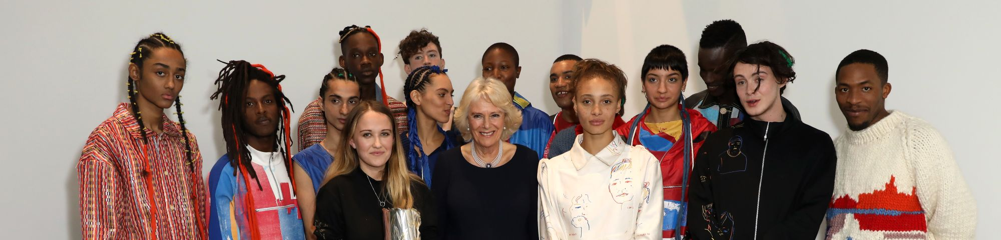 Young designer and royal pose with a group of models