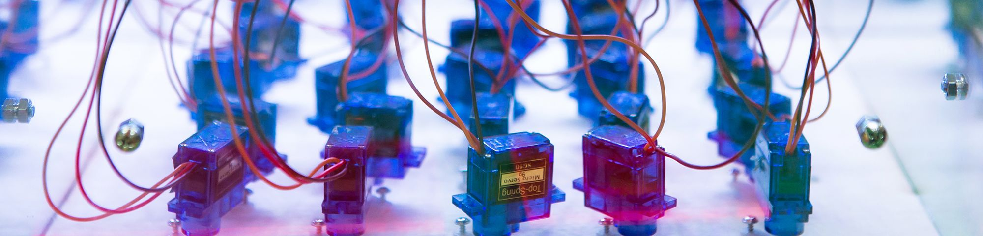 A grid of turquoise and pink electrical cubes with pink wires coming out of them.