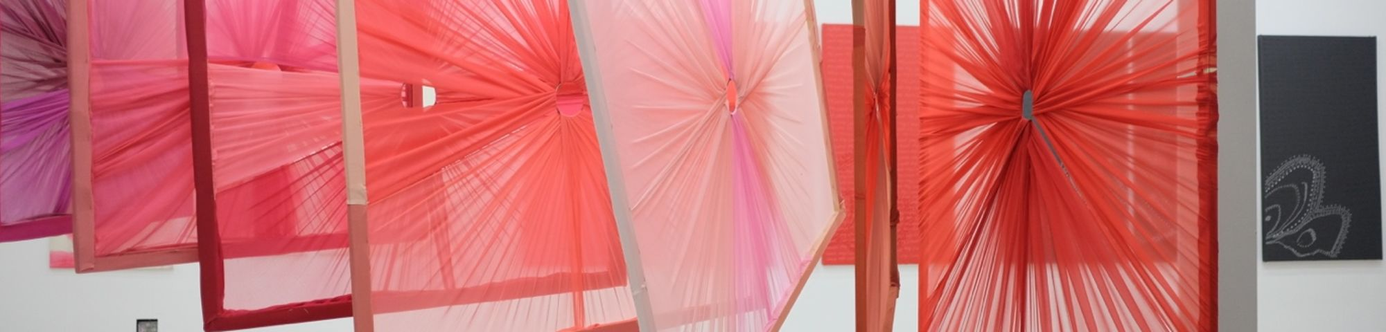 Frames with textile draped around them hanging from the ceiling in a gallery
