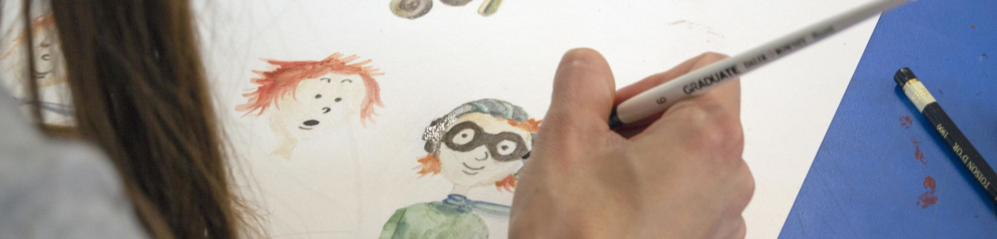 Student working on a character design in watercolour