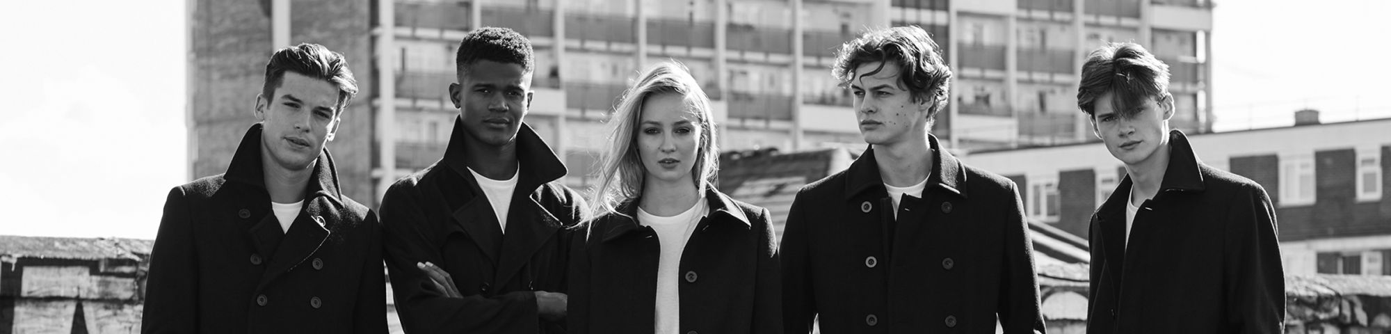 4 male models and 1 female model wearing black and white rustic clothing standing at a block of deserted flats