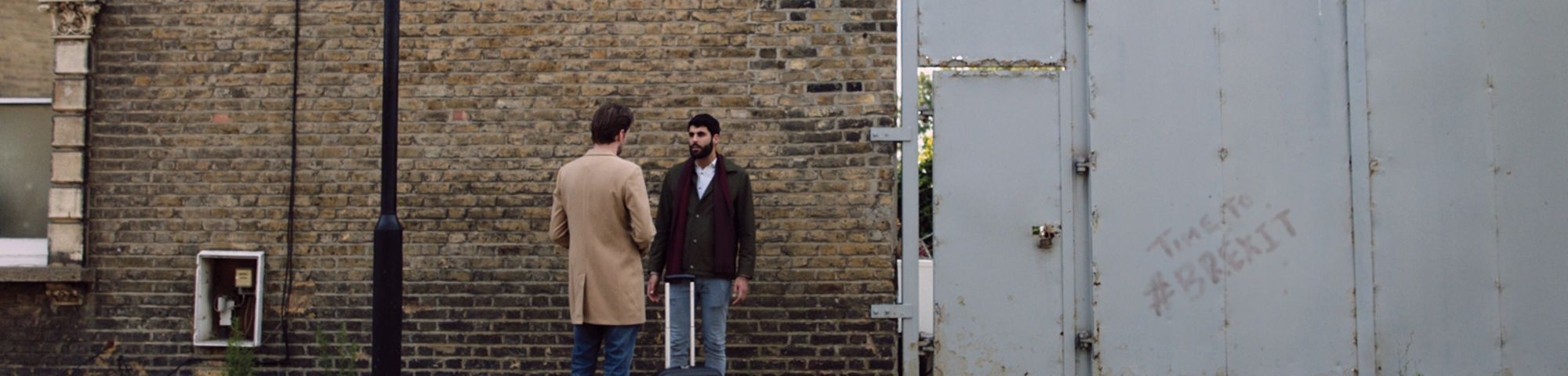 Two men stand and have a conversation in a residential street, one with a suitcase