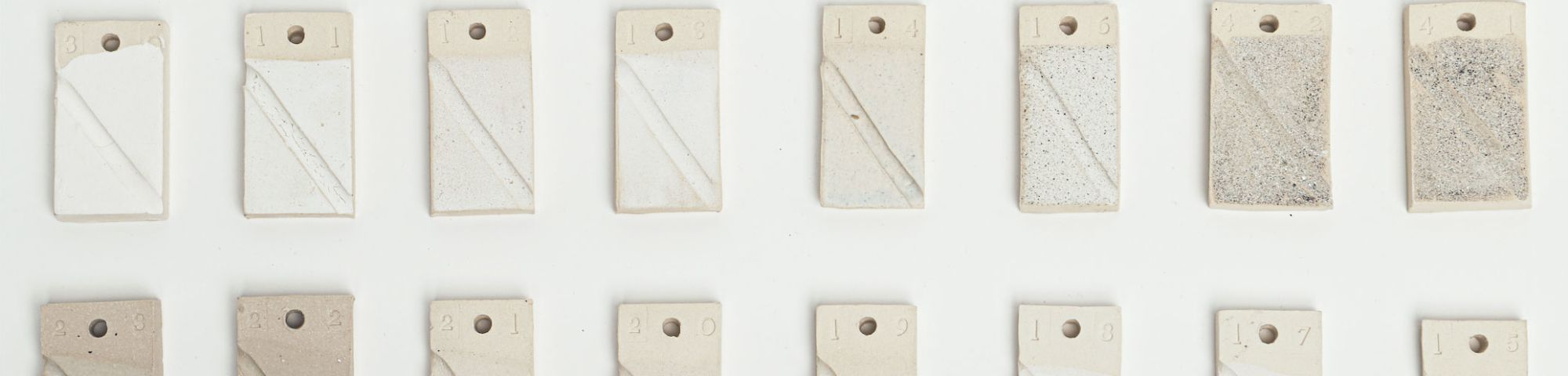 Series of rectangular glaze texts in shades of grey and white
