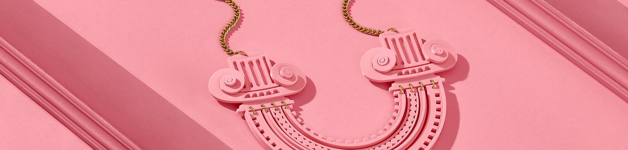 Bright pink photograph of necklace in the form of a chunky cartoon Roman column