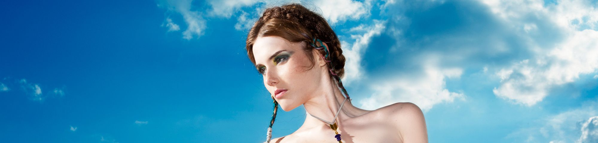 Woman wearing jewellery in front of a blue sky