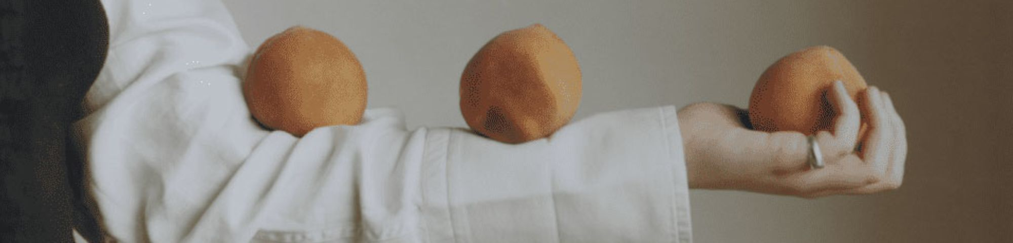 A girl balances three oranges on her arm.