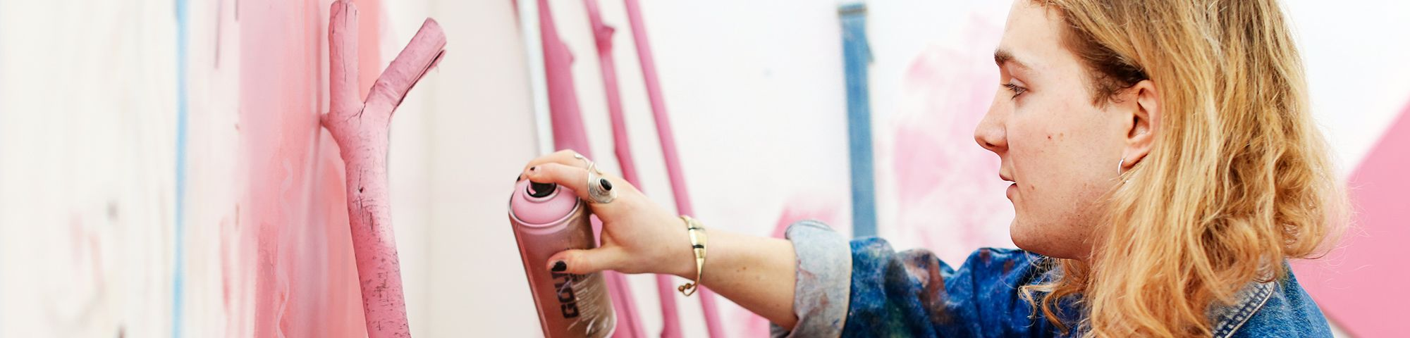 Student using pink spray paint can