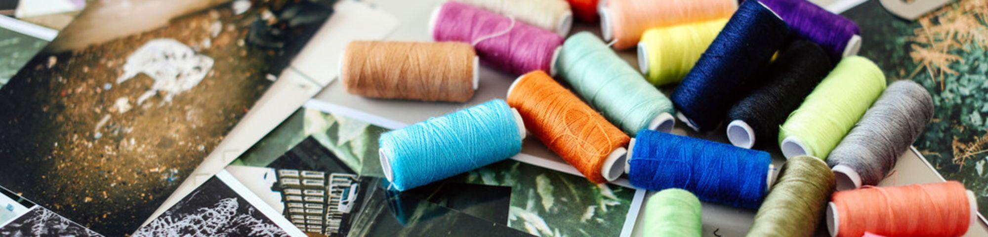 Rolls of thread spread across photos lying on a table