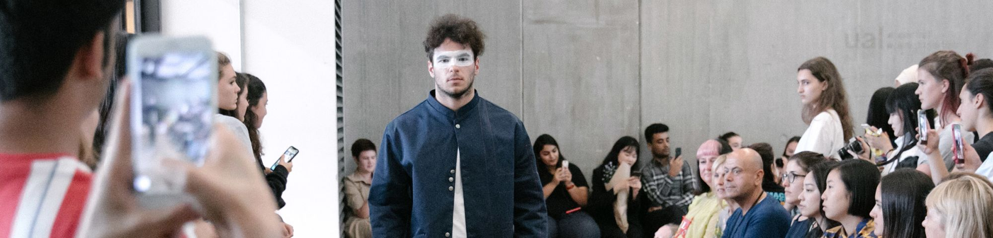 Male model walking down runway with students and staff taking photographs