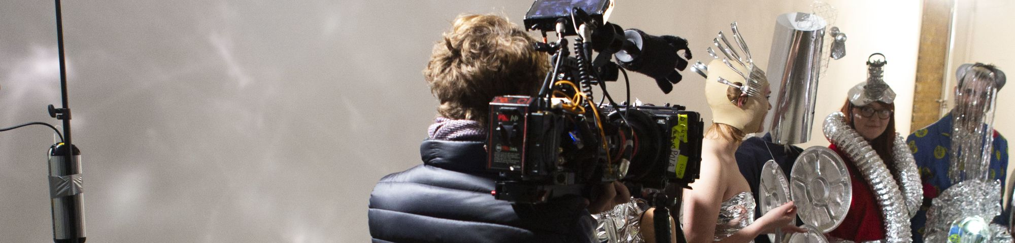 Person holding camera standing in front of people dressed in silver