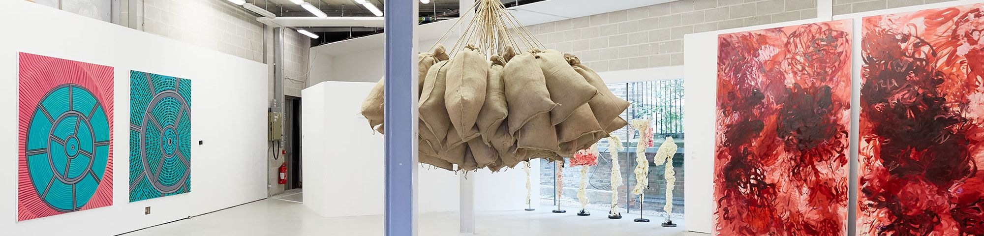 Two sets of paintings and a sculpture of hanging sacks from the ceiling as part of the MA Fine Art Summer Show