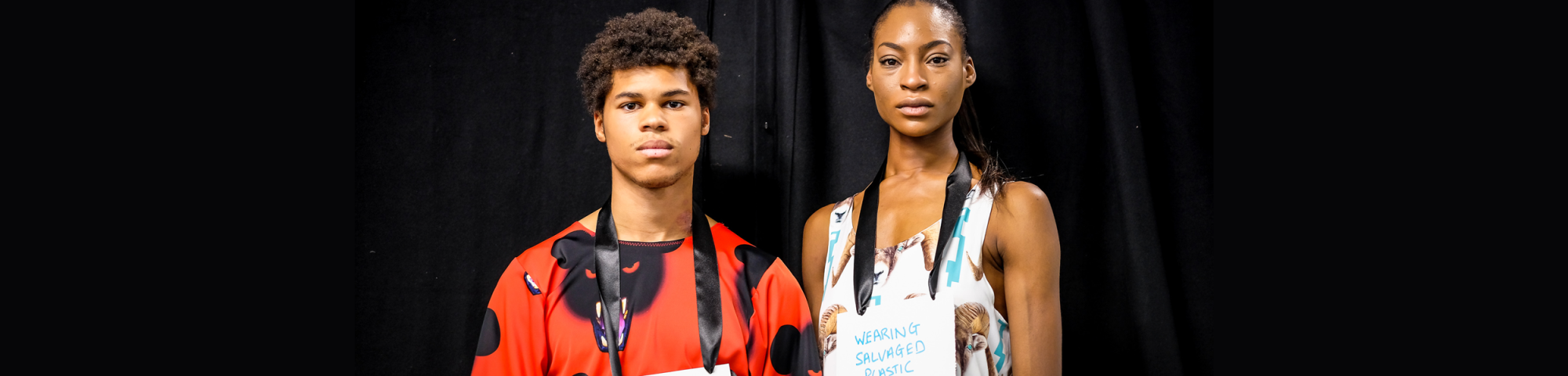 Two models wearing signs saying 'wearing salvaged plastic' from Vin+Omi's LFW presentation