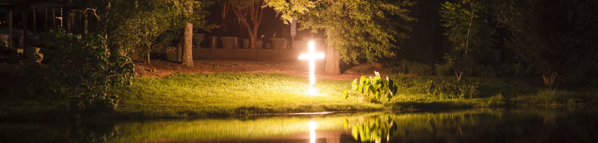 a cross on fire reflected on a lake