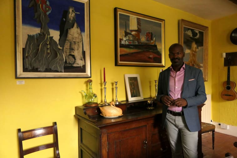 A man stands in a yellow room hung with framed works of art.