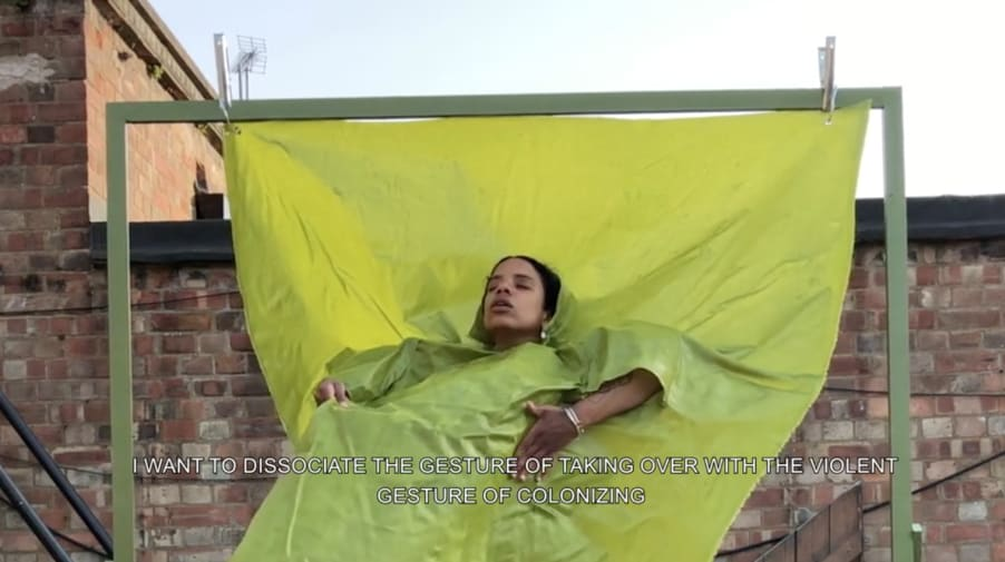 Woman enveloped in green fabric hanging from frame