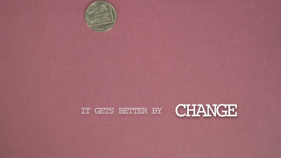 A still of a coin falling in front of a pink background.