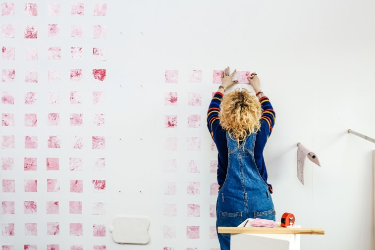 Student creating art on a white wall