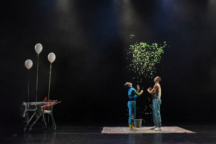 Two performers on stage with green confetti and shopping trolley