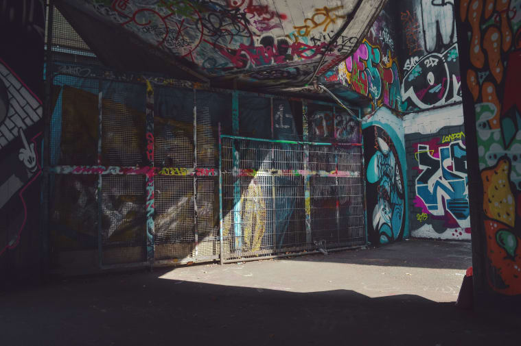 A wall is covered in graffiti in tones of black, blue and pink