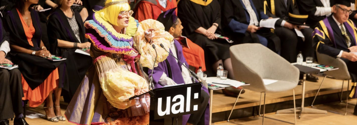 Grayson Perry wearing robes designed by Rachele Terrinoni standing on the stage at graduation
