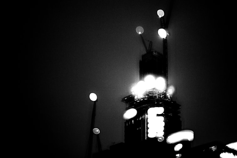 Blurry black and white image of tall building under construction.