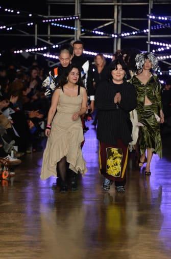 Two women walking down catwalk