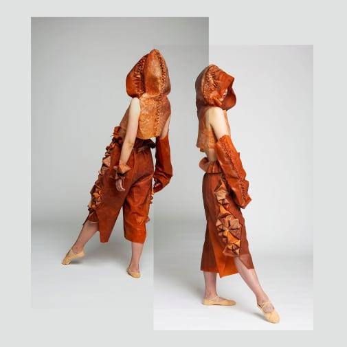 Figures in space wearing orange material garments