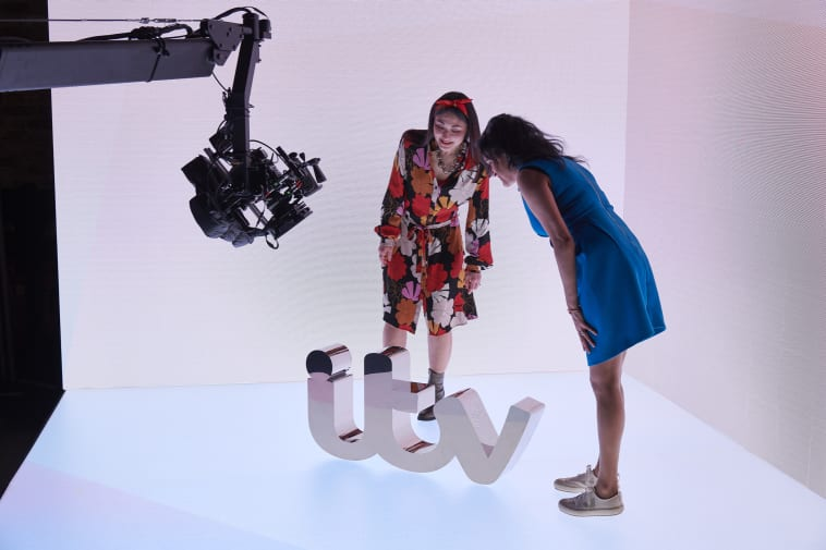 Two women setting up a shot of the mirrored model of the 'itv' logo