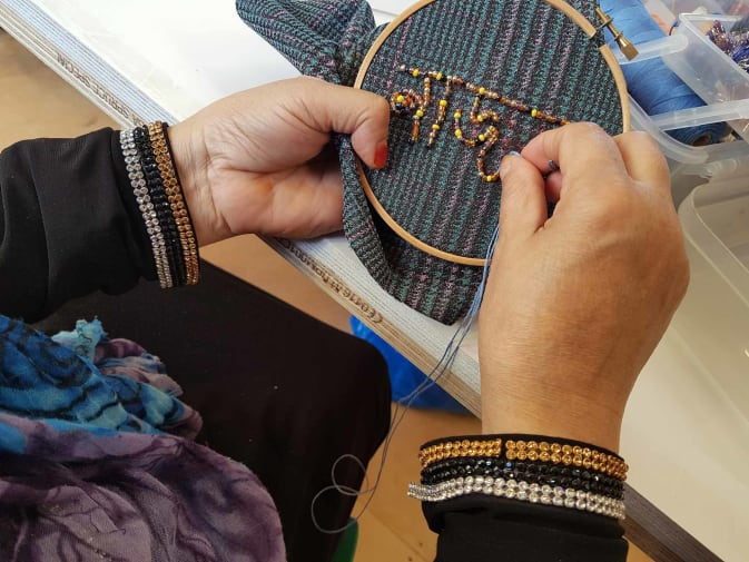 Hand sewing beads into fabric
