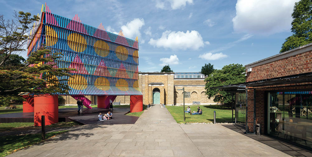 Image depicts a brightly coloured structure, the Colour Palace, erected in front of Dulwich Picture Gallery.