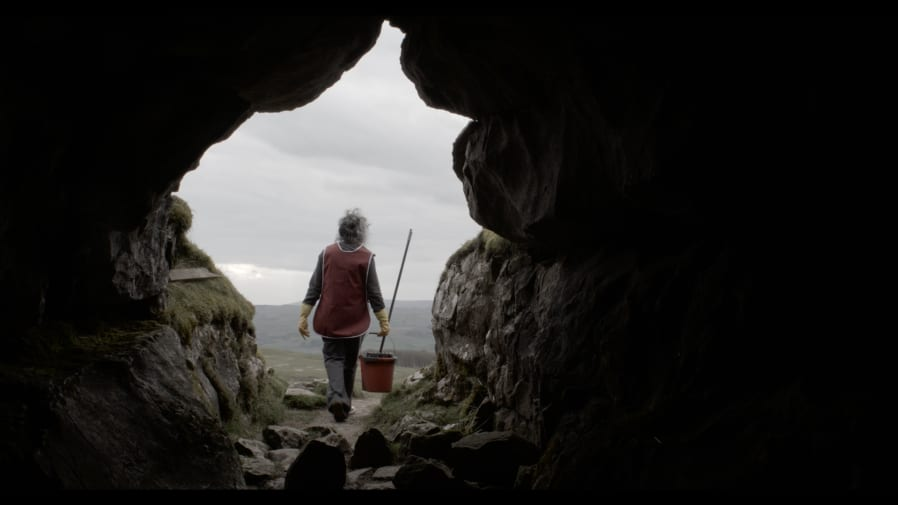 A women stood at the mouth of a cave