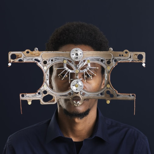 A portrait photo of a man of African descent looking into the camera, wearing oversized, futuristic glasses made out of metal