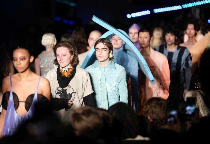 A line of male models walking the catwalk