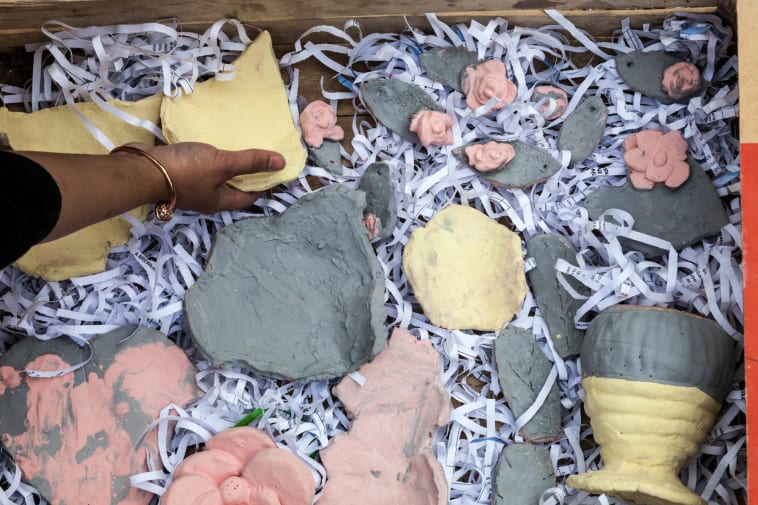 Hand reaching for clay objects