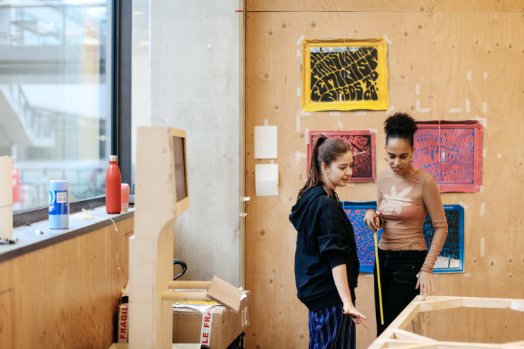 2 female students preparing for an exhibition, one holds a measuring tape, and in the background there are plywood walls and surfaces. There are 2 posters on one of the plywood walls