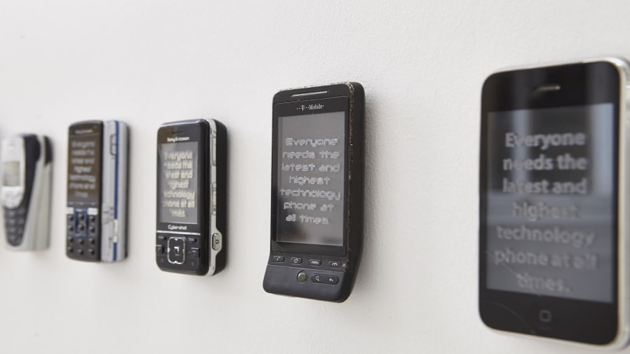 Line of old mobile phones displaying text