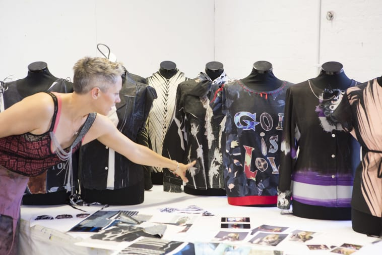 Rebecca Earley in a workshop working with shirts on mannequins and images laid out on a table