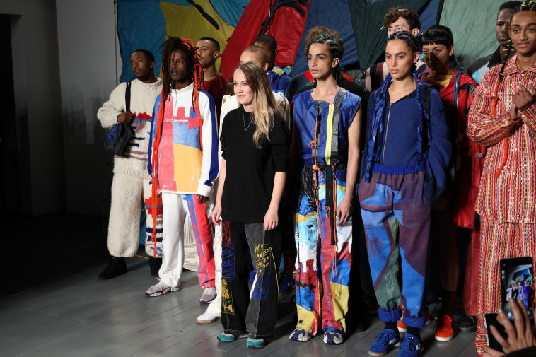 Young designer posing with group of models