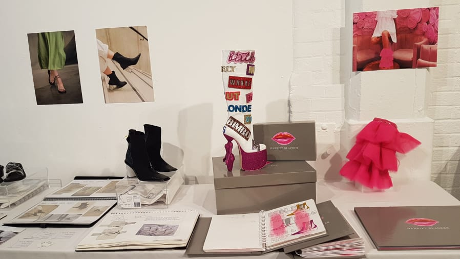A black ankle boot with a concrete white heel stands next to a high heeled knee high boot in pink glitter which has badges on it with words like 'bitch' and 'bimbo.'