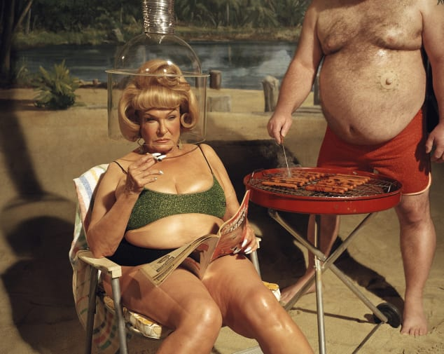 Two plus size models at the beach. One sitting on a lounge chair, holding a cigarette, with a salon hair dryer above their head. The other stands barbecuing hot dogs.