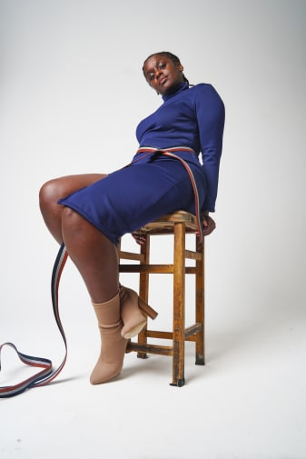 Woman sitting on a bench with a blue dress and light brown boots