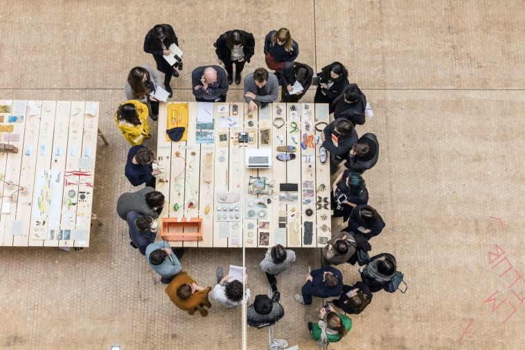 Group of people gathered around a table looking at different objects and devices