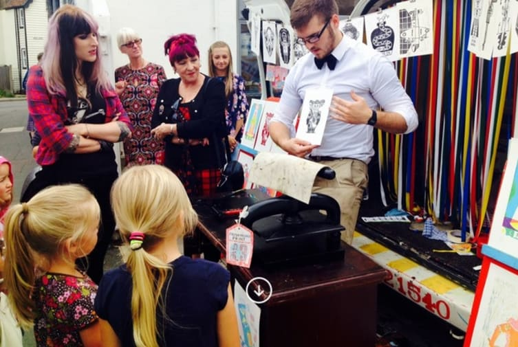 Photograph – Aidan Saunders demonstrating  printmaking with a group