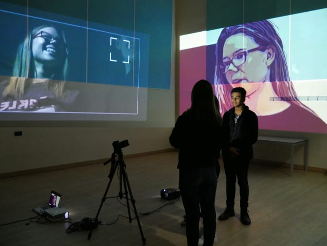 photograph of two students in a dark room with projections of their faces on walls