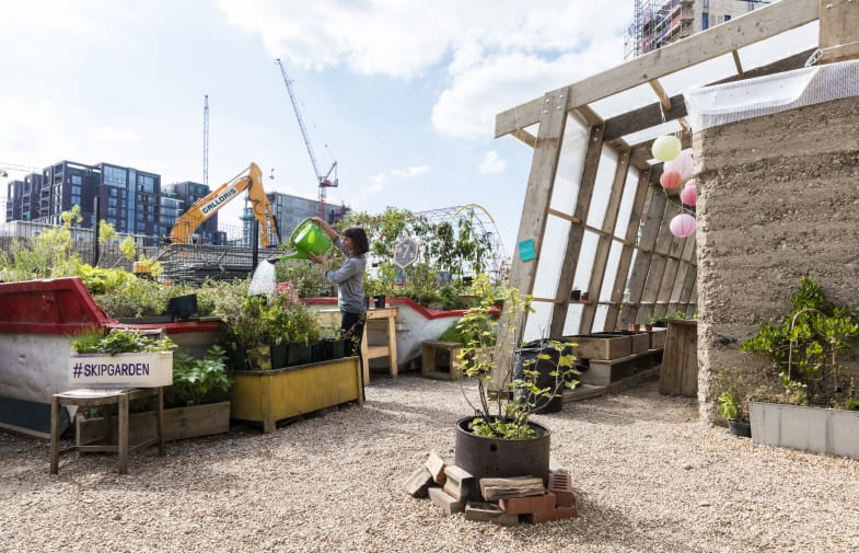City rooftop garden with planters and a person watering plants