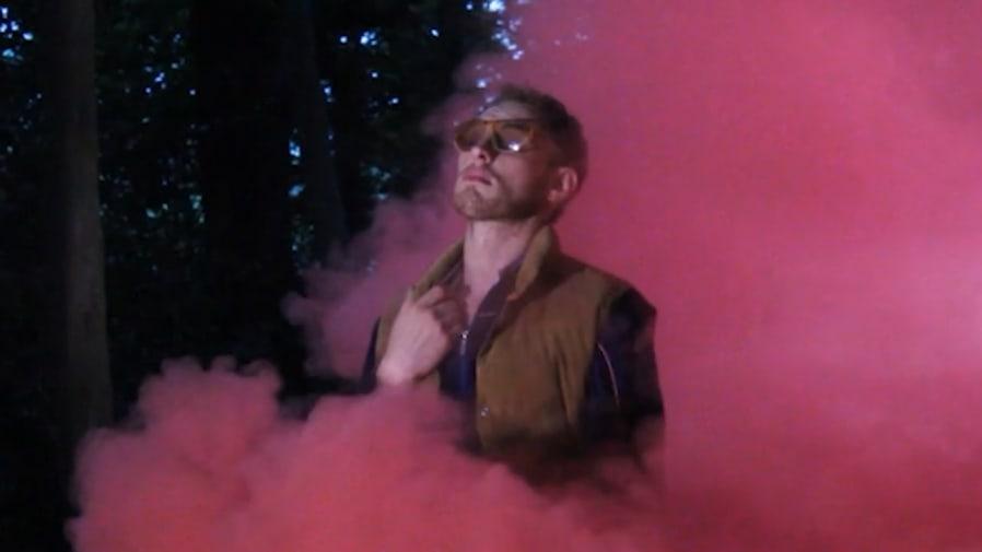 Luke Abbott stood among red smoke wearing sunglasses.