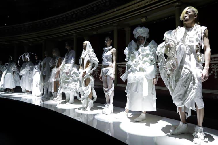 Models wearing white garments standing along catwalk